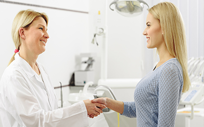 A dentist shaking a female patient's hand