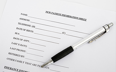 An image of a new patient information form with a pen