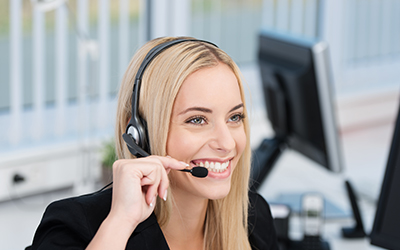 Dental personnel (front office staff) with a headset smiling