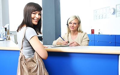 woman standing at the front office desk, with a receptionist beind the desk