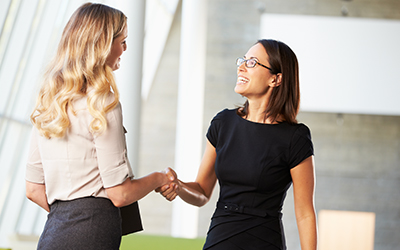 Two business woman shaking hands in an office