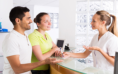 A man and a woman talking with a receptionist in a dental office